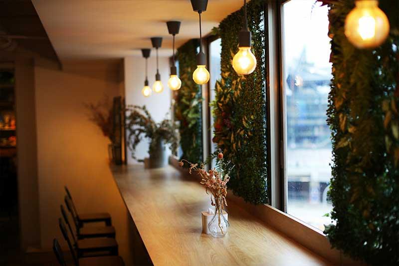 台中文青旅店設計-靠窗吧台用餐區運用綠色植物點綴文青風加成
